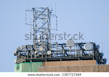 Set of telecommunications/telecoms antenna including RF, PMR, cellular, SDH and PDH microwave dishes on a tall building.