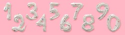 Set of ten Arabic numerals, edible figures made of white royal icing or meringue with colored sugar sprinkles. Top view isolated on pastel pink background. Confectionery decorative design.