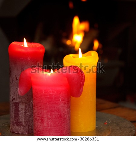 Set of three burning candles in front of a burning fire place