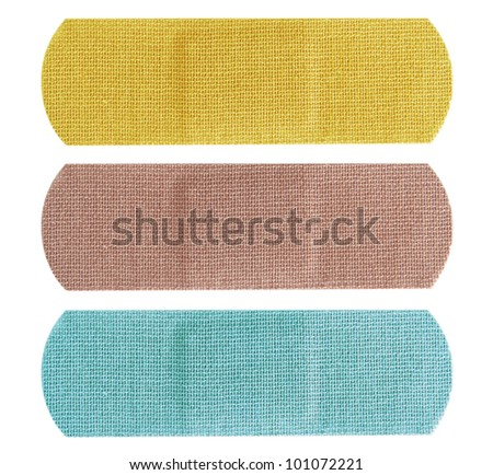 Set of three colored bandaids or bandages in blue, yellow and beige over white.