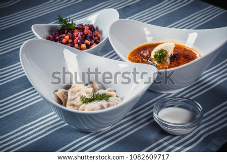 Set of three dishes. Business lunch of three dishes. Three dishes on white plates on a table with a blue tablecloth striped. Soup, salad and hot dish. #1082609717