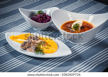 Set of three dishes. Business lunch of three dishes. Three dishes on white plates on a table with a blue tablecloth striped. Soup, salad and hot dish. #1082609726
