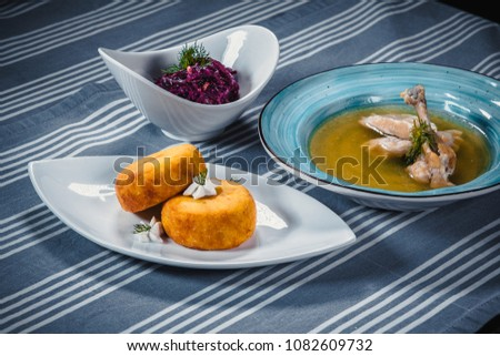 Set of three dishes. Business lunch of three dishes. Three dishes on white plates on a table with a blue tablecloth striped. Soup, salad and hot dish. #1082609732