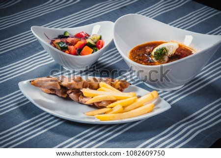 Set of three dishes. Business lunch of three dishes. Three dishes on white plates on a table with a blue tablecloth striped. Soup, salad and hot dish. #1082609750