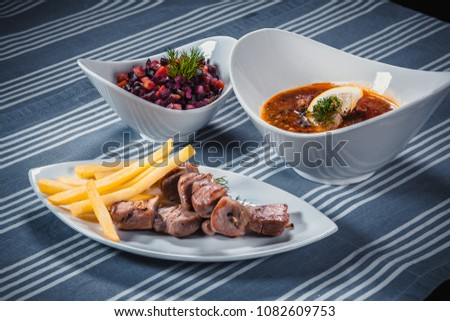 Set of three dishes. Business lunch of three dishes. Three dishes on white plates on a table with a blue tablecloth striped. Soup, salad and hot dish. #1082609753