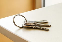 Set of three house keys on the ring on table in a room. Bunch of apartment keys. To forget keys at home consept. Close-up.