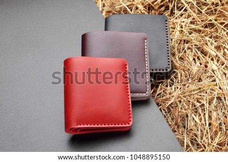 Set of three red brown and black wallet. Hand made leather man wallet . Multi colored. Leather craft.On cretive background .Top view