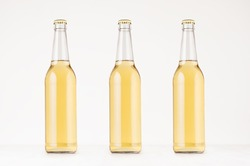 Set of three transparent longneck beer bottle 500ml with lager, mock up. Template for advertising, design, branding identity on white wood table.