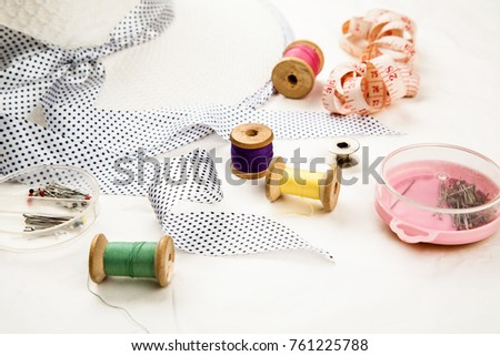 Set of tools and accessories for sewing and needlework with threads in spools, needles, measuring tape and other items on a white background #761225788