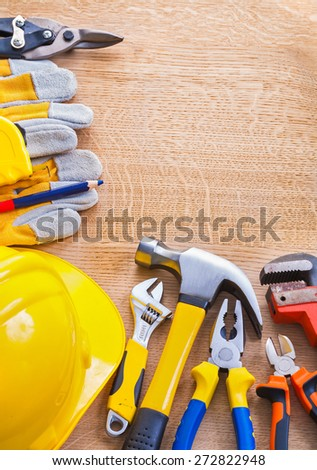 set of tools organized in cpyspace monkey wrench nippers pliers hammer helmet pencil glove cutter on wooden board construction concept