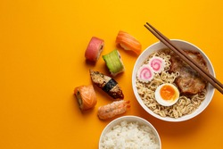 Set of traditional Japanese food: hot soup ramen, boiled white rice, sushi, rolls on bright orange background. Dishes of Japanese cuisine, from above, asian dinner or lunch template, space for text