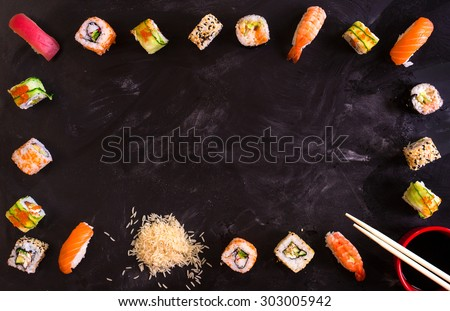 Set of traditional japanese food on a dark background. Sushi rolls, nigiri, raw salmon steak, rice, cream cheese, avocado, lime, pickled ginger. Asian food frame. Dinner party.