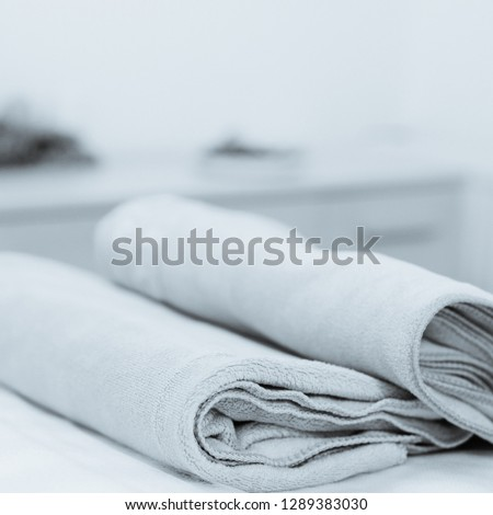 Set of two colorful cotton towels lying on massage table. photo converted in black and white with a blue tint