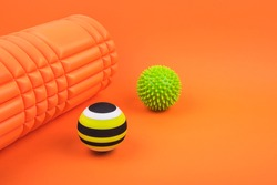 Set of two green myofascial release and massage balls, bumpy foam massage roller for trigger points over burnt orange color background.  Self body care massage and stress, pain relief concept.