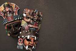 Set of two Mexican Mayan Aztec wood and ceramic mask on black background