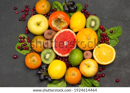 Set of varied, multicolored exotic fruits. Tangerines and oranges, kiwi and pear, persimmon and lychee. Black Background. Flat lay