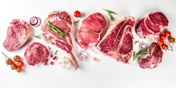 Set of various classic, alternative raw meat, veal beef steaks - chateau mignon, t-bone, tomahawk, striploin, tenderloin, new york steak. Flat lay top view on white table background