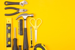Set of various construction tools. Tools for home repair. Work at a construction site. On a yellow background. Flatly. Flatlay.