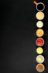 Set of various sauces on a dark background top view with copy space.