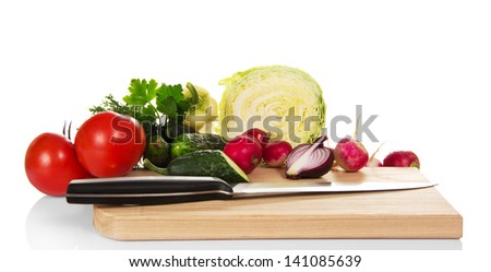 Set of vegetables and knife on the chopping board, isolated on white