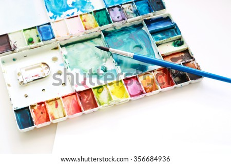 Set of watercolor paints, brushes for painting and blank white water color paper sheet of sketchbook on white background. Creation process of watercolor painting. Top view. #356684936