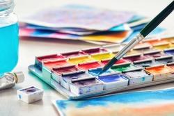 Set of watercolor paints, paintbrush, glass of water and paper sheets of watercolor paintings on background. Selective focus.