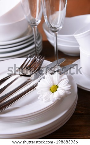Set of white dishes on table on brown background