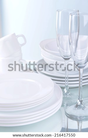 Set of white dishes on table on light background