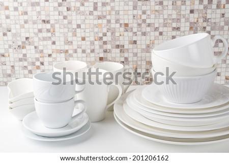 Set of white dishes on white kitchen table