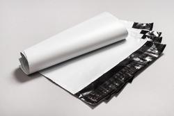 Set of white polythene envelopes on grey background