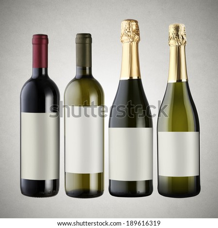 Set of wine bottles on gray background with blank labels.