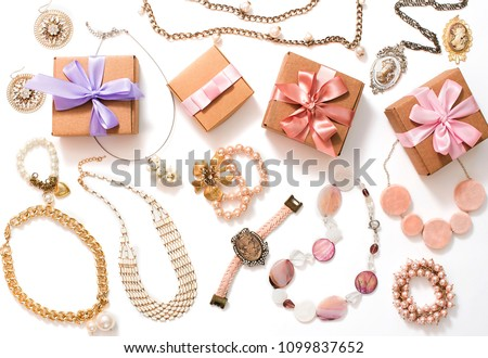 Set of women's jewelry in vintage style necklace cameo pearl bracelet chain earrings on white background. The view from the top lay flat. #1099837652