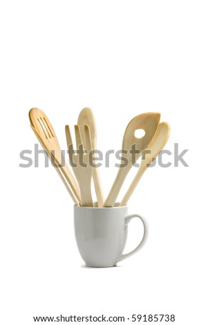 Set of wooden spoons in cup over white background
