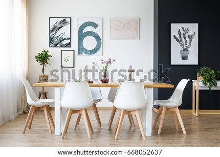 Set of wooden table with white chairs in cozy room