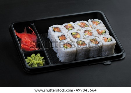 Set salmon rolls in a plastic plate on a black background
