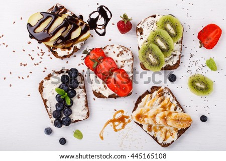 Set sweet sandwiches with cream-cheese and fresh berries and fruit over a white background . Top view. healthy breakfast.selective focus. #445165108