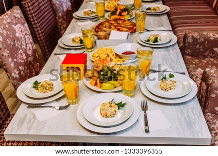 set table for children, round portions of Olivier salad, pizza and orange juice