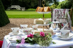 Set table for traditional vintage british afternoon tea with cake, sandwiches and view of green garden