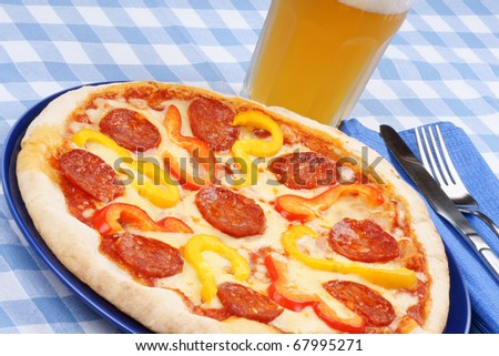 Set table with hot spicy pizza and beer.