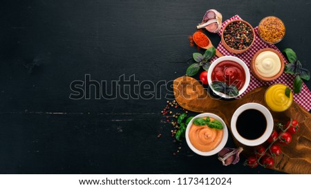 Set the sauces on a black wooden background. Ketchup, mayonnaise, mustard, soy sauce, barbecue sauce, pepper and spices. Top view. Free space for text. #1173412024