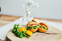 Set variety of tiny little burgers or sandwiches filled with ham, salami, tuna or salmon, served with fresh green lettuce on wooden board with slices of cheese tapas