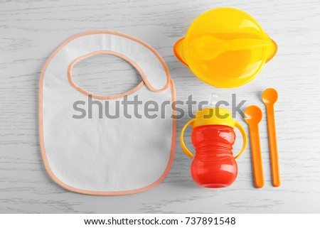 Set with bright baby dishware on table #737891548