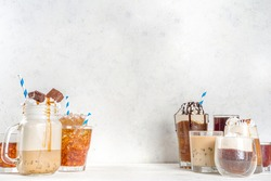 Set with different iced summer coffee drinks - espresso, frappe, latte, cappuccino, with whipped cream, syrup and crushed ice, in various glasses and  mugs on white background copy space