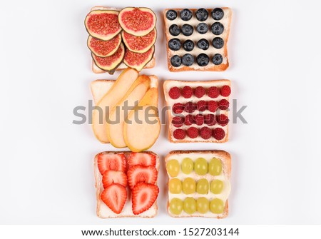 Set with toast and different vegan toppings isolated, top view. Toasts with pear, blueberries, raspberries, grapes, strawberries, figs and other fruit ingridients. Healthy snack concept. Copy space #1527203144