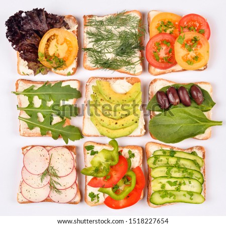 Set with toast bread and different toppings on white background, top view. Toasts with avocado, spinach and other vegetables ingridients. Healthy snack or vegan food concept #1518227654