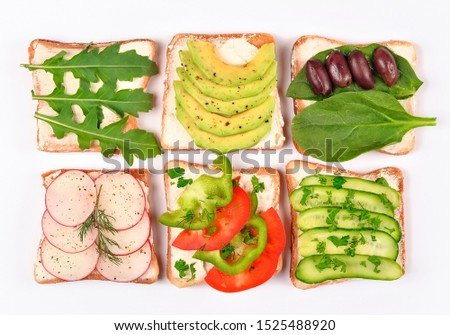 Set with toast bread and different vegan toppings on white background, top view. Toasts with avocado, spinach, arugula and other vegetables ingridients. Healthy snack or vegan food concept #1525488920