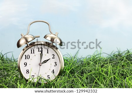 Set your clocks back with this clock in grass against a bright sky. Daylight saving time concept background.