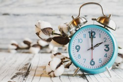 Set your clocks forward and Spring ahead with this clock and bolt of cotton over a white wooden table. Daylight saving time concept. Selective focus with blurred background.