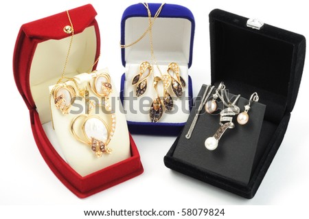 Sets of gold jewelry in open boxes, on white