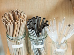 Sets of wooden straws made from bamboo, metal straws from stainless and straw brushes for sustainable lifestyle that is eco friendly and help reduce the trash
